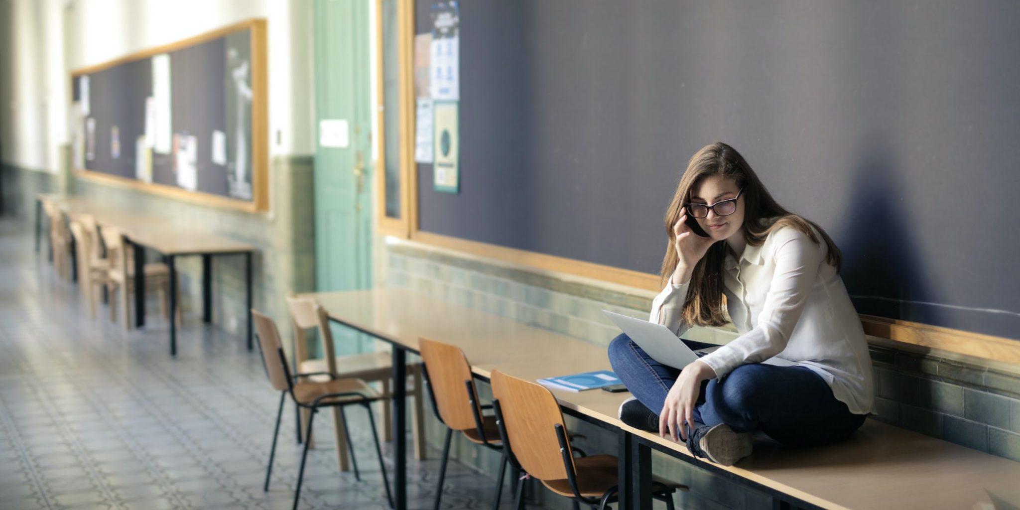 Õpilane istub käsi põsakil koolis laua peal rätsepaistmes ja vaatab süles olevat arvutit. Pildi autor: Andrea Piacquadio Pexelsist.