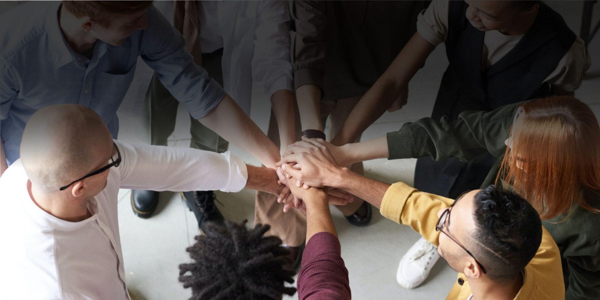 Meeskond on ringis ja käsi teineteise käte peal kuhjas. Pildi autor: Fauxels Pexelsist.